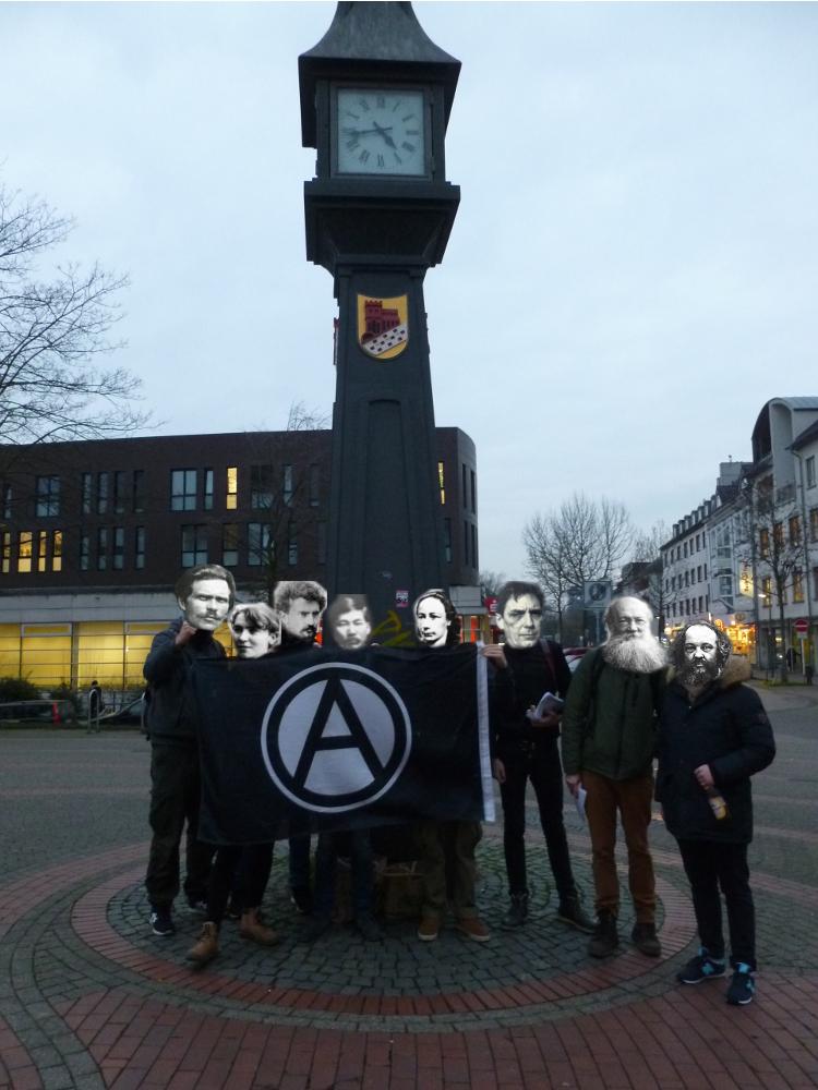 [Foto: Anarchist_innen vor anarchistischer Flagge]