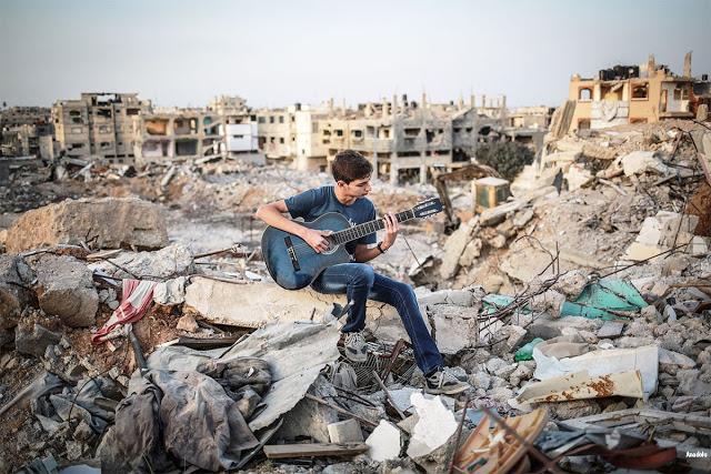 [Foto: Junge spielt Gitarre auf Trümmern]